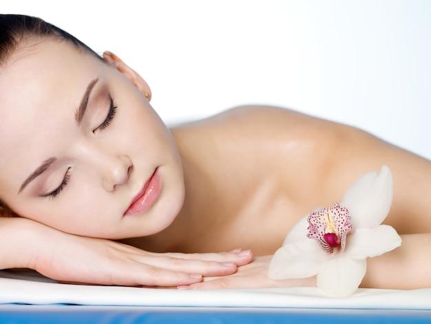 Porträt der ruhenden jungen schönen frau im schönheits-spa-salon mit blume