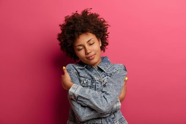 Porträt der ruhigen attraktiven frau schließt die augen, umarmt sich