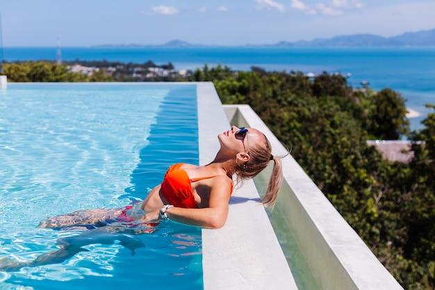 Porträt der ruhigen glücklichen frau in der sonnenbrille mit gebräunter haut im blauen schwimmbad am sonnigen tag