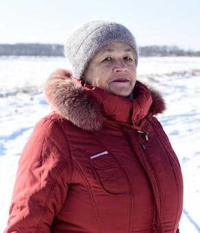Porträt der russischen älteren frau, die kamera gegen schneebedecktes feld betrachtet