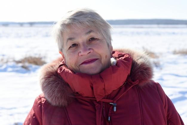 Porträt der russischen älteren frau, die lächelt und kamera betrachtet