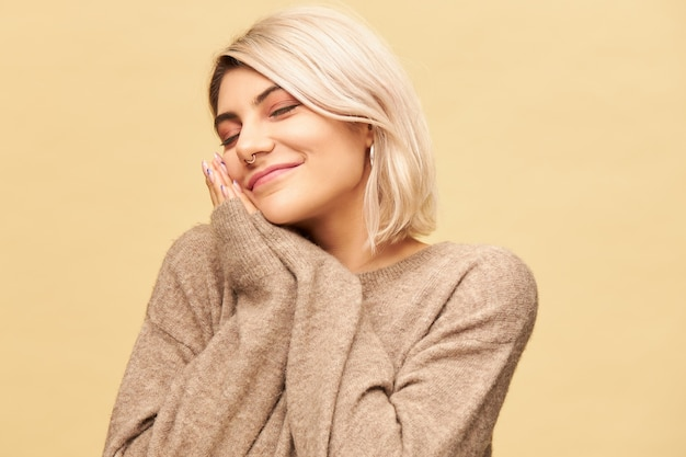 Porträt der schläfrigen müden jungen blonden frau mit dem nasenring, der den kopf auf zusammengepresste hände legt und die augen geschlossen hält, ein nickerchen macht oder schläft und glücklich lächelt. schlaf-, bett- und müdigkeitskonzept
