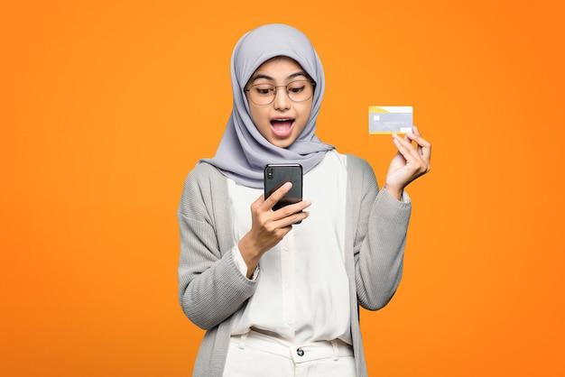 Porträt der schockierten asiatischen frau, die kreditkarte und handy hält