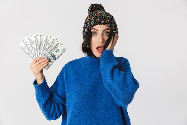 Porträt der schockierten frau, die wintermütze hält, die fan des dollargeldes beim stehen hält, lokalisiert auf weiß