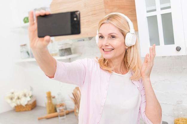 Porträt der schönen älteren frau, die ein selfie nimmt