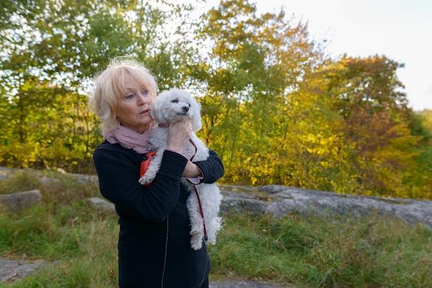 Porträt der schönen älteren frau mit den kurzen blonden haaren, die im park draußen im herbst entspannen