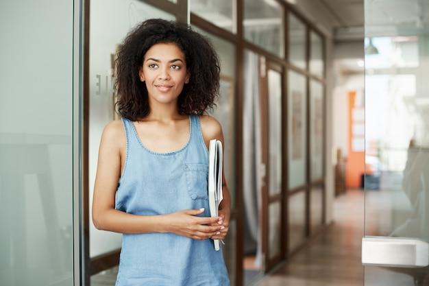 Porträt der schönen afrikanischen studentenfrau, die im college-korridor lächelnd hält bücher hält, die in seite schauen. bildungs- und lernkonzept.