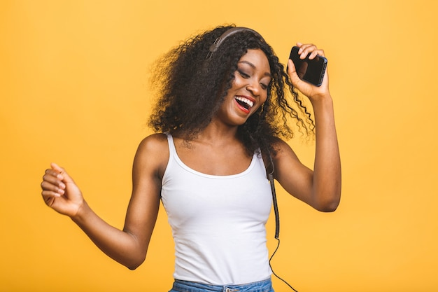Porträt der schönen afroamerikanerfrau, die musik hört