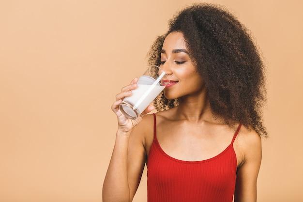 Porträt der schönen afroamerikanerfrau mit glas milch
