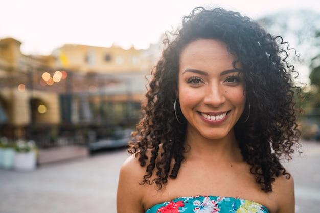 Porträt der schönen afroamerikanischen lateinamerikanischen selbstbewussten frau, die in der straße lacht. draußen.