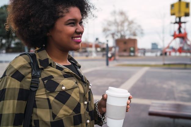 Porträt der schönen afroamerikanischen lateinischen frau, die eine tasse kaffee draußen in der straße hält. stadtkonzept.
