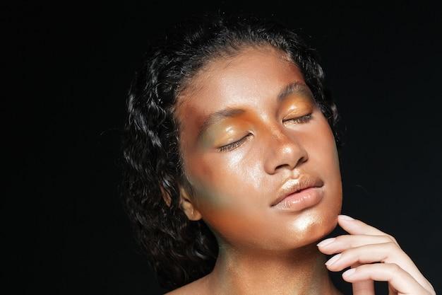 Porträt der schönen amerikanischen jungen frau mit stilvollem make-up über schwarz