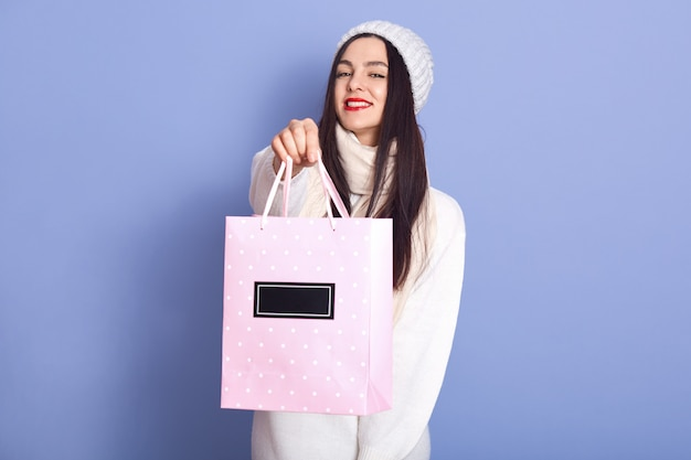 Porträt der schönen angenehmen frau, die rosa papiertüte mit kauf hält, mit langen schwarzen haaren