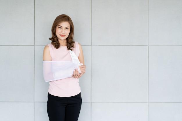 Porträt der schönen asiatin, frau des gebrochenen arms im krankenhaus mit kopienraumabschluß oben.