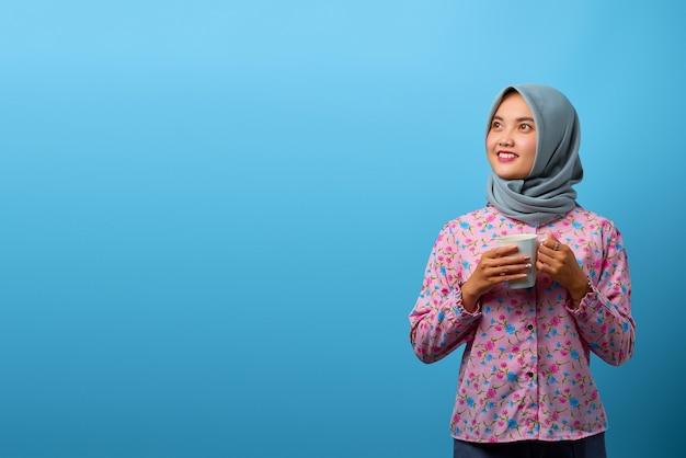 Porträt der schönen asiatischen frau, die becher mit glücklichem lächeln genießt und hält