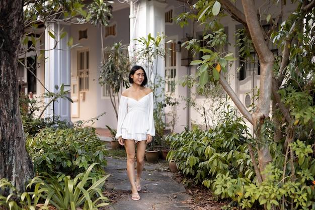 Porträt der schönen asiatischen frau, die draußen in einem weißen kleid aufwirft