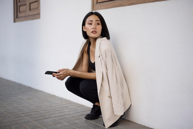 Porträt der schönen asiatischen frau, die draußen smartphone benutzt