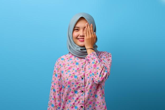 Porträt der schönen asiatischen frau, die ein auge mit der hand mit glücklichem lächeln bedeckt