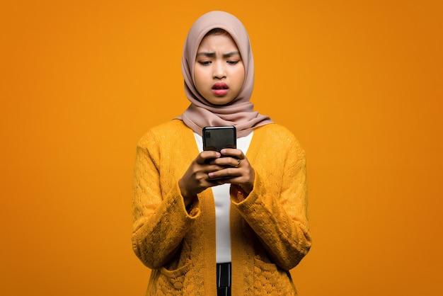 Porträt der schönen asiatischen frau, die ein smartphone mit einem gelangweilten ausdruck verwendet