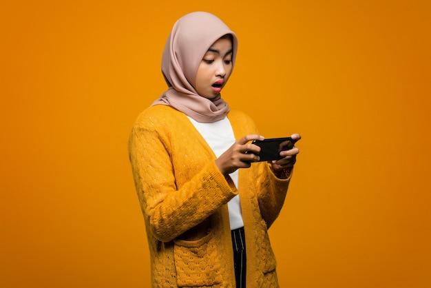 Porträt der schönen asiatischen frau, die ein videospiel auf einem smartphone mit einem schockierten ausdruck spielt