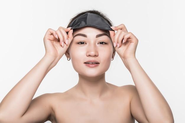 Porträt der schönen asiatischen frau, die eine schlafmaske trägt, die auf weißer wand lokalisiert wird