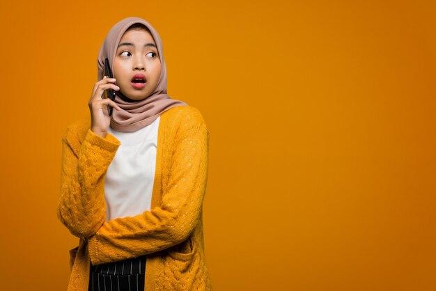Porträt der schönen asiatischen frau, die handy mit einem freund und schockiertem gesicht spricht