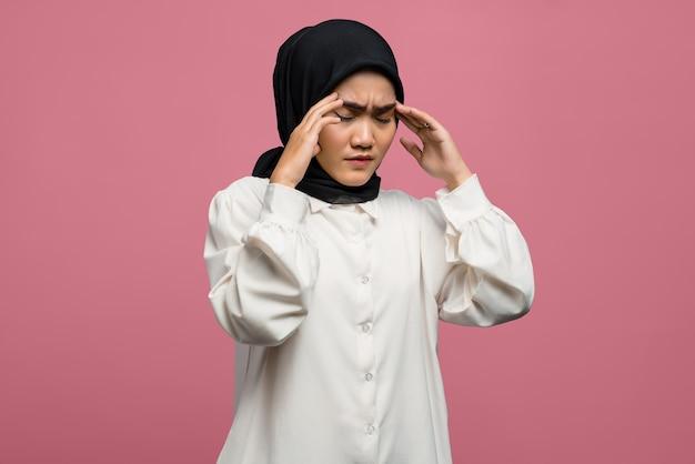 Porträt der schönen asiatischen frau, die kopfschmerzen fühlt