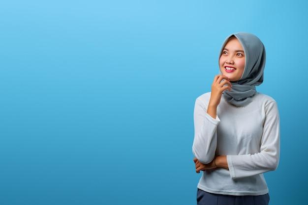 Porträt der schönen asiatischen frau, die mit der hand am kinn auf blauem hintergrund lächelt