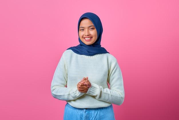 Porträt der schönen asiatischen frau, die mit der hand zusammen auf blauem hintergrund lächelt