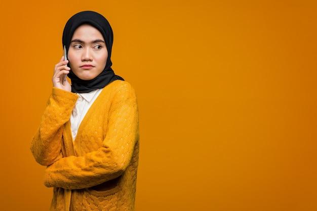 Porträt der schönen asiatischen frau, die mit einem freund auf handy spricht