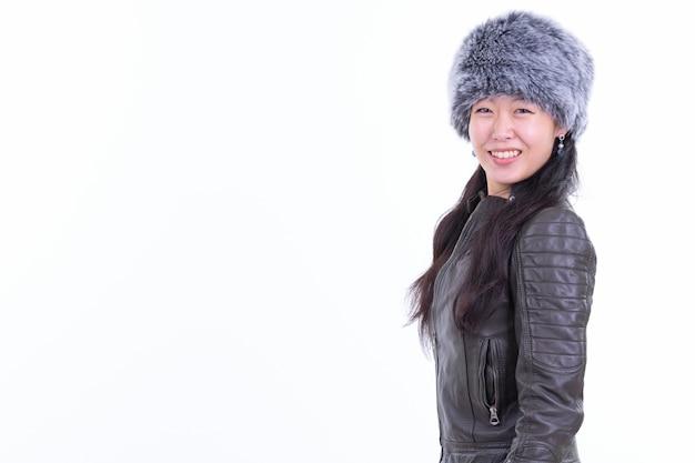 Porträt der schönen asiatischen frau, die pelzmütze bereit für winter lokalisiert auf weiß trägt