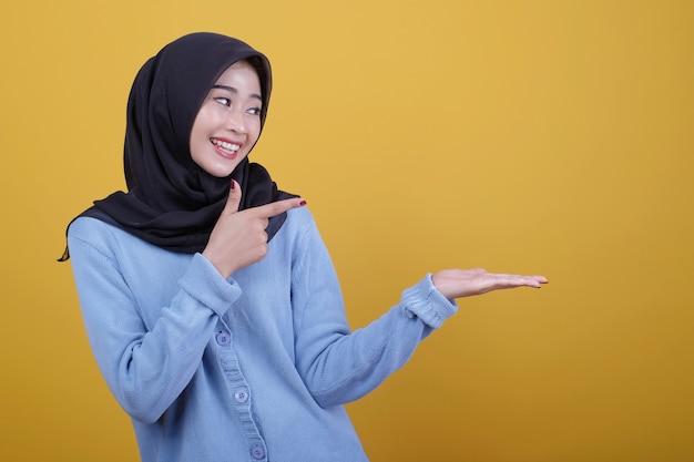 Porträt der schönen asiatischen frau, die schwarzen hijab trägt, blickt glücklich ausdruck, der mit zeigefinger zeigt und zeigt