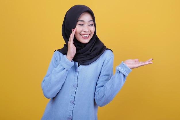 Porträt der schönen asiatischen frau, die schwarzen hijab trägt, sagen sie etwas geflüstertes und zeigen sie etwas Premium Fotos