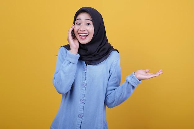 Porträt der schönen asiatischen frau, die schwarzen hijab trägt, sagen sie etwas geflüstertes und zeigen sie etwas