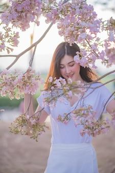 Porträt der schönen asiatischen frau, die tabebuia rosea im park halten lächelt. glückliche frau. sonnenlichteffekt bild