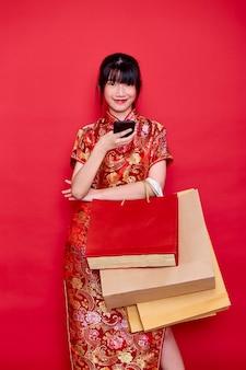 Porträt der schönen asiatischen frau, die traditionelles cheongsam qipao kleid trägt, das smartphone mit einer einkaufstasche in der hand auf einem roten hintergrund für chinesische neujahrseinkaufskonzepte zeigt