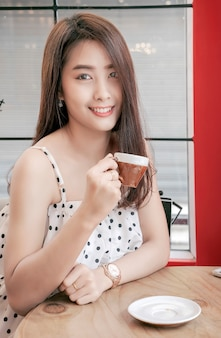 Porträt der schönen asiatischen frau haben einen tasse kaffee beim sitzen einer kaffeestube.