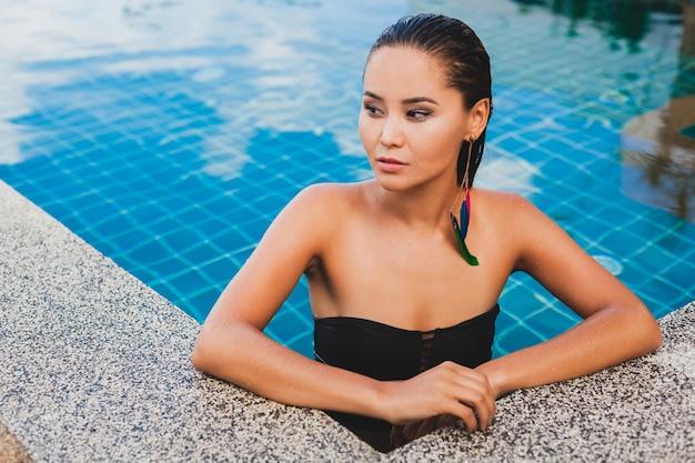 Porträt der schönen asiatischen frau im schwarzen badeanzug, der luxus-spa-swimmingpool badet und lächelnden sylischen federohrring trägt, sexy, schlank gebräunter körper und nasse haut, accessoires im sommerstil,