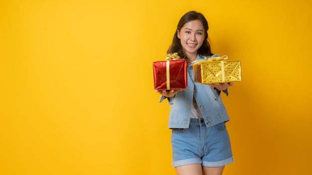 Porträt der schönen asiatischen frau in jeanskleidern, die geschenkbox halten