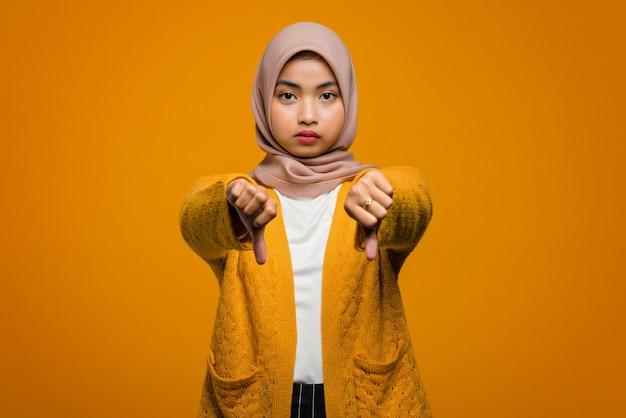 Porträt der schönen asiatischen frau lächelnd daumen zeigen, missbilligen und etwas nicht mögen