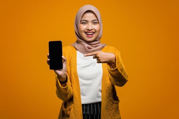 Porträt der schönen asiatischen frau lächelnd und auf smartphone zeigend