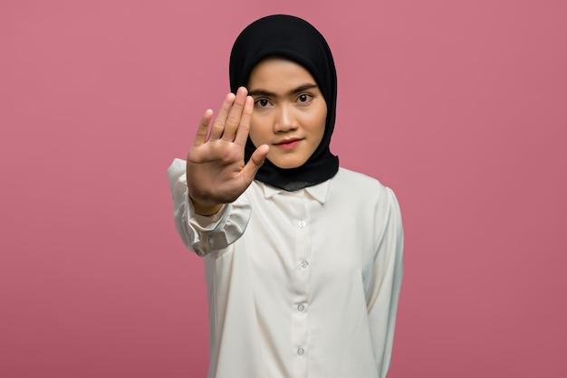 Porträt der schönen asiatischen frau mit offener hand, die stoppschild tut
