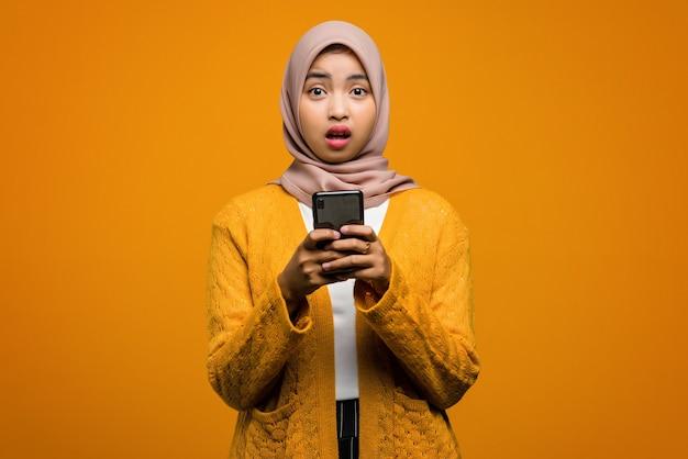 Porträt der schönen asiatischen frau schockiert und mit einem smartphone