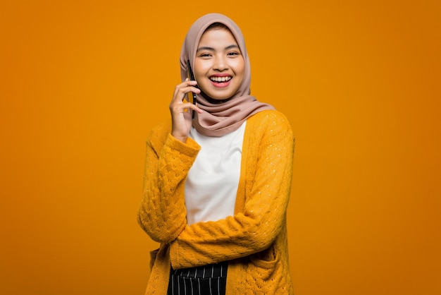 Porträt der schönen asiatischen frau unter verwendung des mobiltelefons, das mit einem freund mit einem glücklichen gesicht und lachen spricht