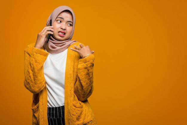 Porträt der schönen asiatischen frau unter verwendung des mobiltelefons, das mit einem freund spricht und sich gelangweilt fühlt