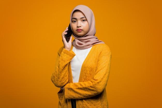 Porträt der schönen asiatischen frau unter verwendung des mobiltelefons, das mit einem freund spricht