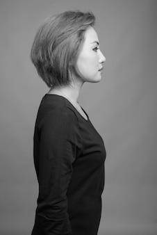 Porträt der schönen asiatischen geschäftsfrau auf grau in schwarzweiss