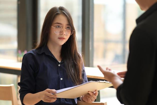 Porträt der schönen asiatischen geschäftsfrau, die schreibarbeit beim treffen hält