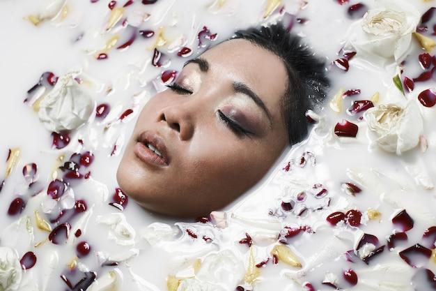 Porträt der schönen asiatischen jungen frau in einem milchbad