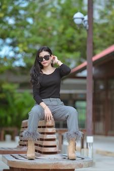 Porträt der schönen asiatischen jungen frau oder der thailändischen jungen frauen in einer luxus-suite, frau ist glücklich im park an einem erholsamen urlaub